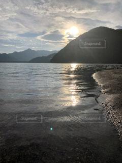 背景に山のある水の体の写真・画像素材[4876100]