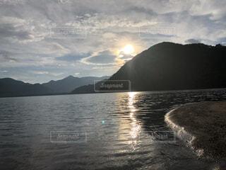 背景に山のある水の体の写真・画像素材[4876102]