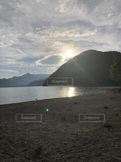 背景に山のある水の体の写真・画像素材[4876104]