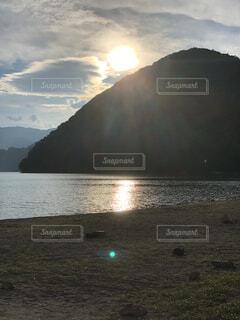 背景に山のある水の体の写真・画像素材[4876105]