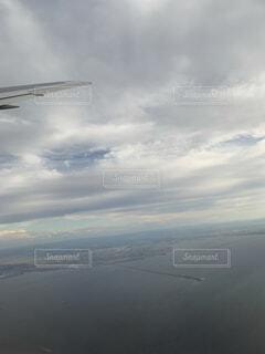 曇りの日に空中を高く飛ぶ大型飛行機の写真・画像素材[4879119]