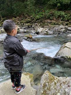 川の隣に立っている少年の写真・画像素材[4879215]