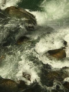 水の中のサーフボードに波に乗っている男の写真・画像素材[4872563]