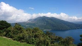 背景に山のある水の体の眺めの写真・画像素材[4872434]