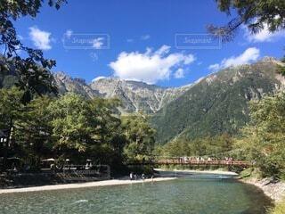 背景に山のある水の体の写真・画像素材[4875971]