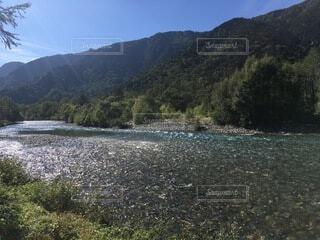 背景に山のある水の体の写真・画像素材[4875974]