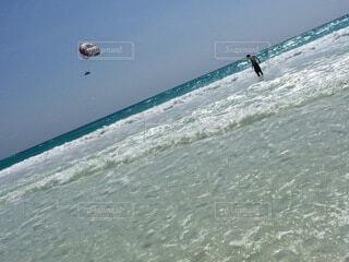 海の隣のビーチで凧を飛ばす人々のグループの写真・画像素材[4876045]