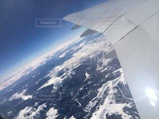 雪に覆われた山の上を飛んでいる飛行機の写真・画像素材[4879151]