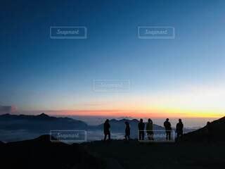水の体の隣に立っている人々のグループの写真・画像素材[4898674]