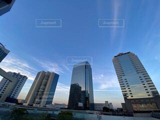 さりげない飛行機雲とビルの写真・画像素材[4874604]