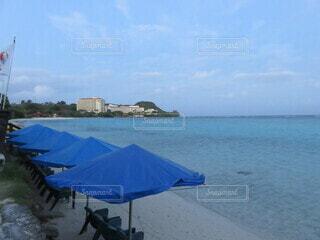 砂浜の上に座っている青い傘の写真・画像素材[4874663]