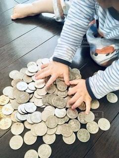 沢山の500円を触る子供の写真・画像素材[4894295]