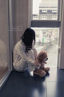 ウィンドウの横に座っているクマのぬいぐるみを持った女性の写真・画像素材[1742248]