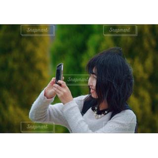 写真を撮る女性の写真・画像素材[1109537]
