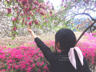 花の前に立っている人の写真・画像素材[1132196]