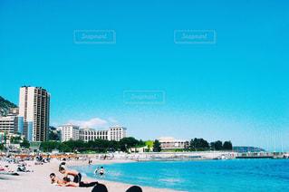 水の体の近くのビーチの人々 のグループの写真・画像素材[1253869]