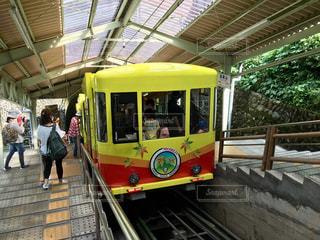 黄色い電車駅に引っ張って横に立っている人々 のグループ - No.814056