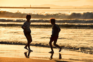朝日に染まる浜辺で、はしゃぐ子供達の写真・画像素材[801613]