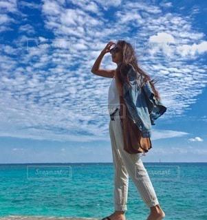 水の体の横に立っている人の写真・画像素材[172]