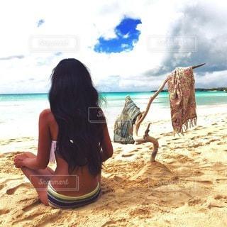 水の体の横にある砂浜に座る人の写真・画像素材[177]