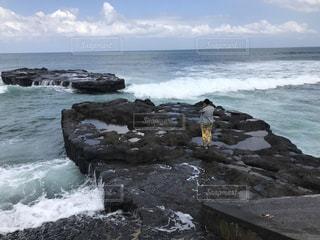 海の横にある岩のビーチの人々 のグループの写真・画像素材[764997]