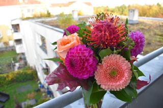 テーブルの上のピンクの花で一杯の花瓶の写真・画像素材[1618364]