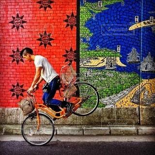 建物の前に自転車を持つ男 - No.393