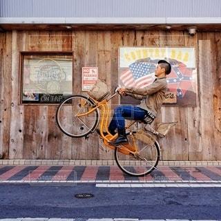 自転車の男は建物の脇に駐車の写真・画像素材[392]