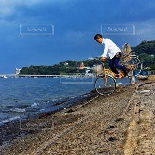 水の近くの未舗装の道路を自転車に乗る男 - No.391