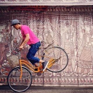 建物の前に自転車を持つ男 - No.380