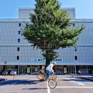 建物の前で自転車に乗る男の写真・画像素材[370]