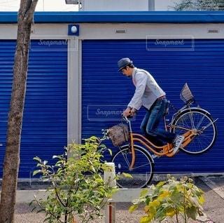 建物の前に自転車を持つ男 - No.358