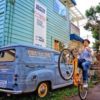 建物の前に自転車を持つ男の写真・画像素材[357]