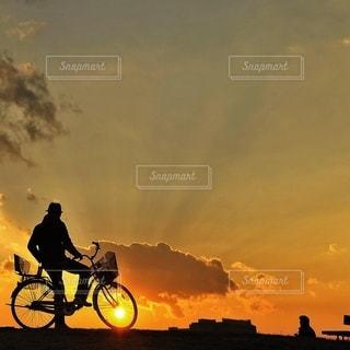 背景の夕日と自転車に乗る男の写真・画像素材[354]