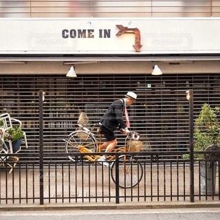 建物の前で自転車に乗る男 - No.339