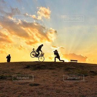背景の夕日とフィールドの人々 のグループの写真・画像素材[333]