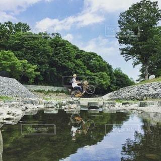 水の体の横に立っている人の写真・画像素材[332]