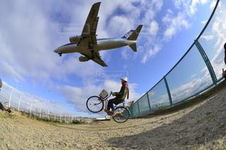 未舗装の道路を自転車に乗りながら空気を通って飛んで人 - No.302