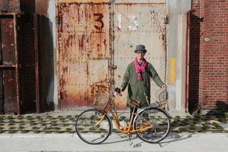 建物の前に自転車を持つ男 - No.298