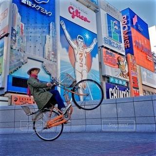 建物の前に自転車を持つ男 - No.287