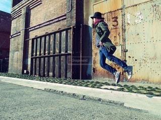 建物の側面の下のスケート ボードに乗る男の写真・画像素材[280]