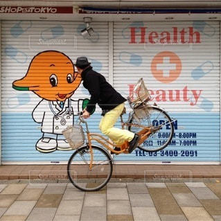 看板の近くの自転車の男の写真・画像素材[400]