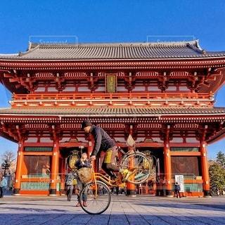 建物の前で自転車に乗る男 - No.352