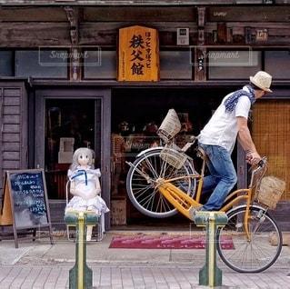 建物の前で自転車に乗る男 - No.329