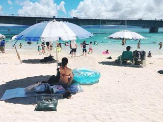 砂のビーチ パラソルに座っている人々の写真・画像素材[1503334]