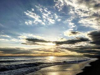 海の横にあるビーチに沈む夕日の写真・画像素材[729793]