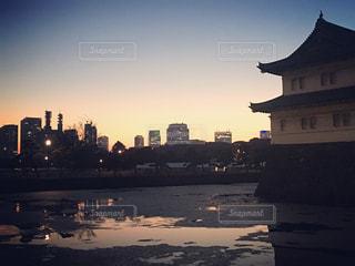 背景の夕日の大型ビルの写真・画像素材[729815]