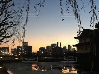 バック グラウンドで市と水体に沈む夕日の写真・画像素材[729817]