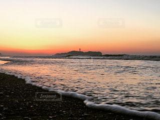 海の横にあるビーチに沈む夕日 - No.730709