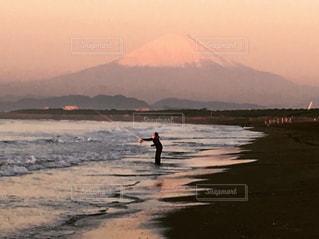 水の横にあるビーチの上を歩く男の写真・画像素材[730800]